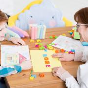 Happy little boy having speech problem. Speech therapist helping her patient to read